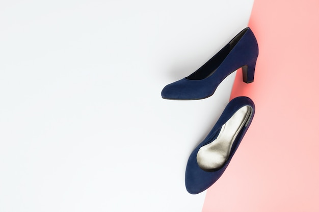 Fashionable blue high heels shoes made of faux leather on pink and white