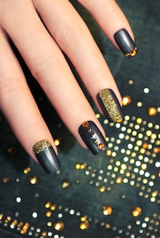 Fashionable blue manicure on square shaped nails with golden sequins
