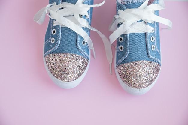 ピンクの壁に分離された女の子のためのファッショナブルな青いスニーカー。トレンディなキッズスポーツシューズのペア。子供向けのトレンディなデニムスニーカー。白いレースのトレンディな光沢のあるスニーカーのペア。ユーススタイル