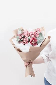 여자의 손에 붉은 난초와 유행 꽃다발. 생일 및 기타 휴일 선물로 아름다운 꽃.