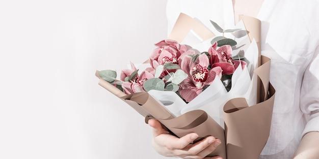 여자의 손에 붉은 난초가 있는 세련된 꽃다발 생일 선물로 아름다운 꽃