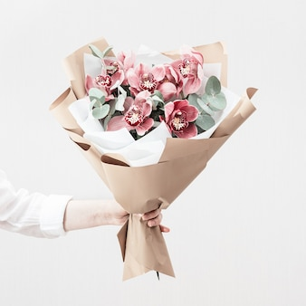 女性の手に赤い蘭のファッショナブルな花束。贈り物としての美しい花