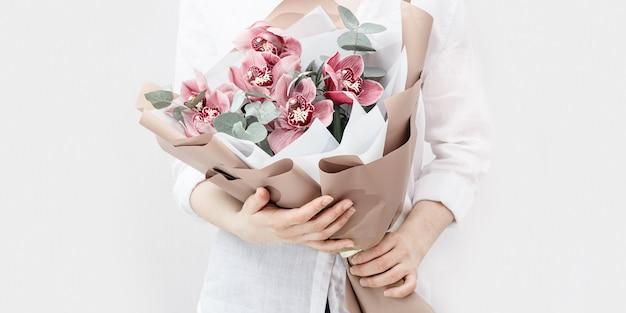 女性の手に赤い蘭とファッショナブルな花束