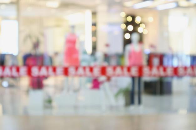 ショッピングモールのファッショナブルなブティック衣料品店のウィンドウディスプレイは、焦点がぼけた背景をぼかします
