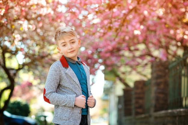 Модный мальчик в весеннем парке. мода, образ жизни и весна. красивый стильный мальчик позирует на фоне цветущей сакуры.