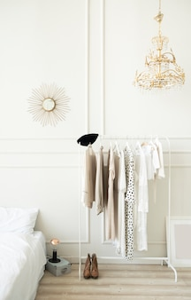 Fashionable bright bedroom interior. hanger with women's clothing.
