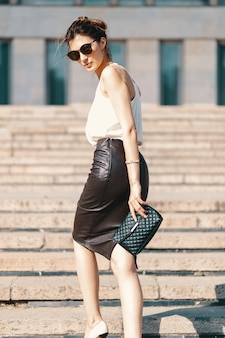 Fashionable brunette businesswoman in leather pencil skirt