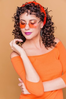 Fashionable brunette girl in a bright orange sweater, glasses and a bandana posing on orange
