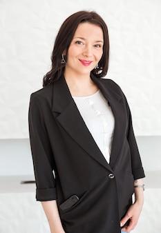 Модная брюнетка девушка в черной куртке позирует на белом фоне. девушка смотрит в камеру и улыбается.