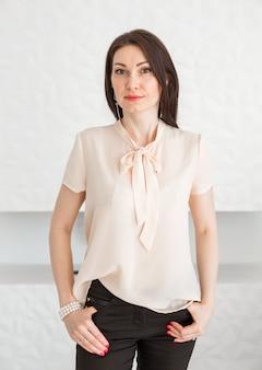 Модная брюнетка в легкой блузке стоит у белой стены, позирует и смотрит в камеру