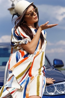 Fashionable brunette girl near the car