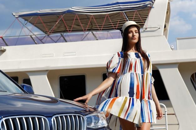 Модная брюнетка девушка возле машины Premium Фотографии