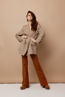 スタジオのベージュの背景にコートのズボンとブーツのファッショナブルなブルネット