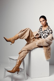 Модная брюнетка в осенней одежде коричневой модели сапог.