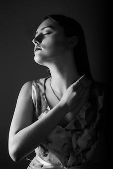 暗い部屋でポーズをとる完璧なメイクと長い髪のファッショナブルなブルネットモデル。モノクロショット