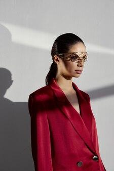 Модная брюнетка с украшением головы в очках костюм красный пиджак обрезанный вид Premium Фотографии