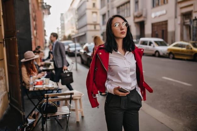 시간을 보내는 사무실 복장에 유행 갈색 머리 여자, 도시 주변 산책