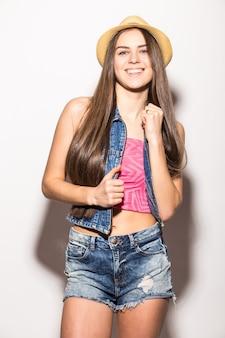 밀짚 모자와 선글라스에 유행 갈색 머리 여자는 흰 벽 위에 절연 미소