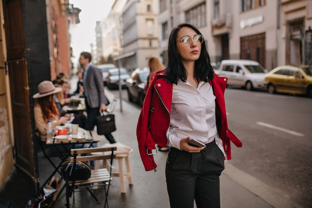 Fashionable brunette woman in office attire spending time, walking around city
