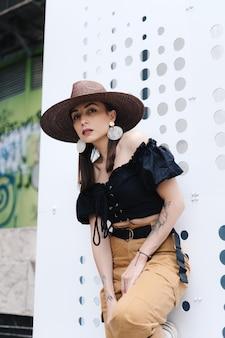 長い髪のファッショナブルなブルネットの女性、スタイリッシュな大きな籐の帽子をかぶって、穴のある白い壁にポーズをとる。