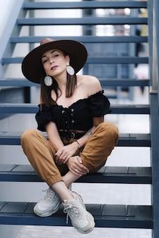 長い髪のファッショナブルなブルネットの女性、スタイリッシュな大きな籐の帽子をかぶって、階段でポーズをとる。
