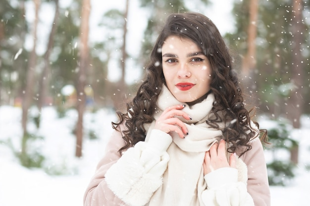 Fashionable brunette woman with long hair wears coat in snowy weather. space for text