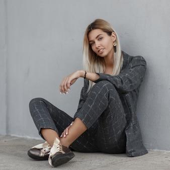 세련된 비즈니스 아가씨. 패션 빈티지 회색 정장에 아름 다운 세련 된 젊은 여자는 회색 벽 근처에 앉아