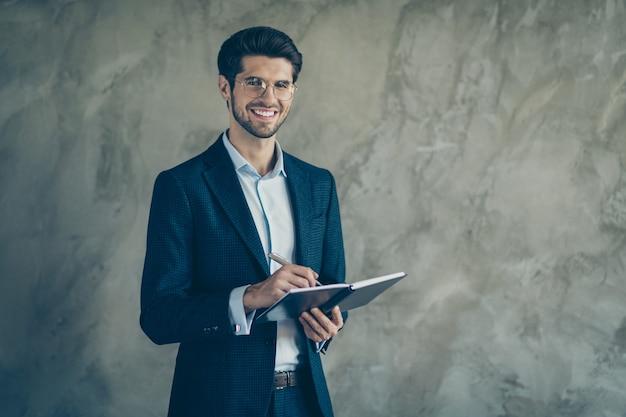 Fashionable businessman posing against the grey wall