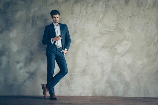 灰色の壁にポーズをとってファッショナブルなビジネスマン