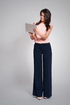 Donna di affari alla moda utilizzando la tavoletta digitale