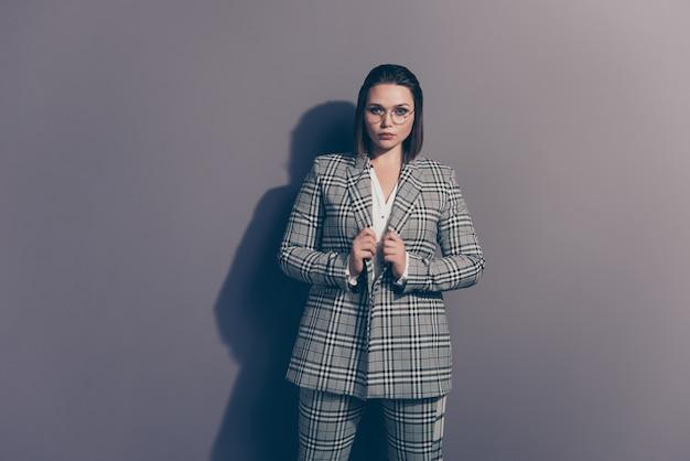 Модная деловая женщина в клетчатом пиджаке позирует в помещении