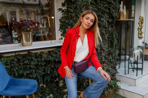 Donna bionda caucasica alla moda in giacca rossa alla moda che gode del fine settimana in caffè
