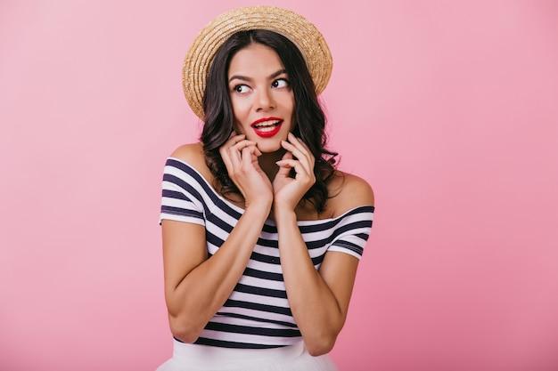진지한 감정으로 포즈 검게 그을린 피부를 가진 유행 백인 여자. 모자에 우아한 곱슬 여자의 초상화입니다.