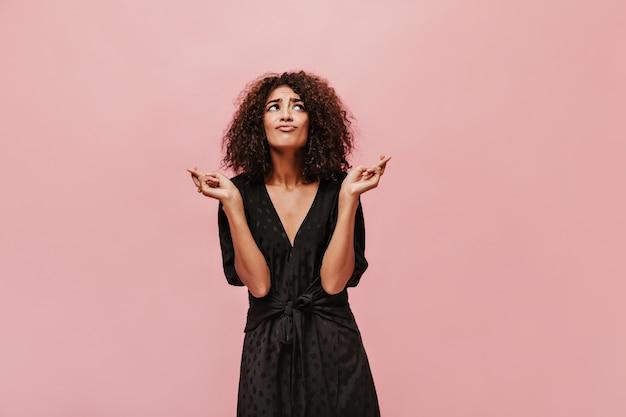 Signora affascinante alla moda con l'acconciatura castana ondulata in vestito nero a pois fresco che guarda in su e incrocia le dita