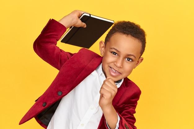 Bambino alla moda con giacca sportiva rossa che tiene un blocco note