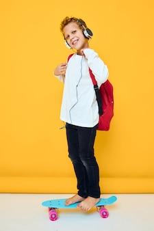 ヘッドフォン黄色の背景でスケートボードとファッショナブルな子供