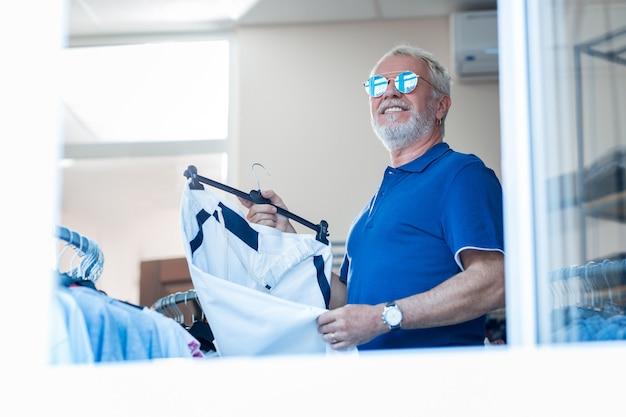 おしゃれな服。スポーツパンツを手に持ってファッショナブルなサングラスを通して目をそらしている陽気な老人