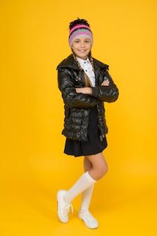세련된 옷은 그녀를 따뜻하게 유지합니다. 노란색 배경에 세련된 가을 모습을 한 행복한 학생입니다. 유행 모자와 코트에 작은 소녀 미소. 세련되고 세련된.