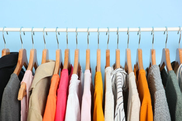 Модная одежда на вешалках на вешалке на цветном фоне