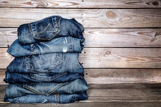 おしゃれな服。木製の背景にジーンズの山