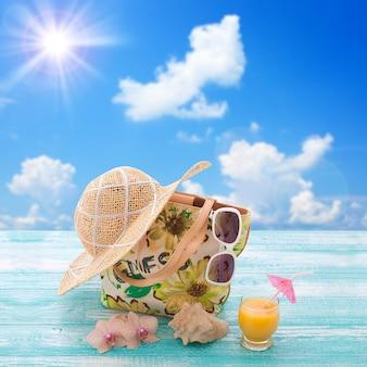 해변 휴가를 위한 세련된 옷 선글라스, 모자, 슬리퍼. 오렌지 주스. 디자인을 위한 평면 조롱. 평면도. 여름 휴가 개념입니다.