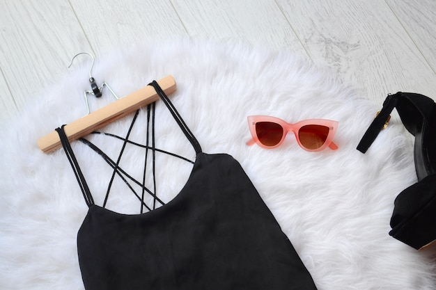Fashionable concept, a black dress and pink sunglasses on the white fur. top view
