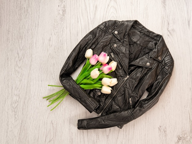 Fashionable concept. black leather jackets, tulips on a wooden background. top view