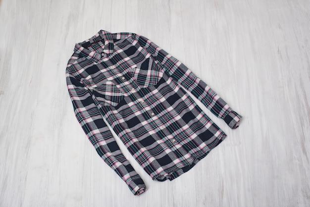 ファッショナブルなコンセプト。木の表面にチェックのシャツ。女性用ワードローブ