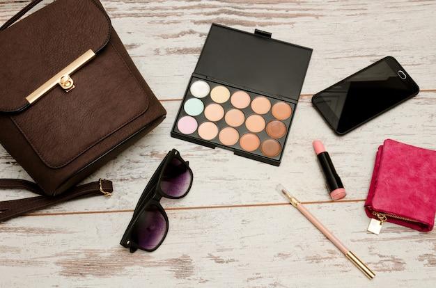 유행 개념 : 아이 섀도우, 핸드백, 안경, 립스틱, 나무 배경에 지갑. 평면도
