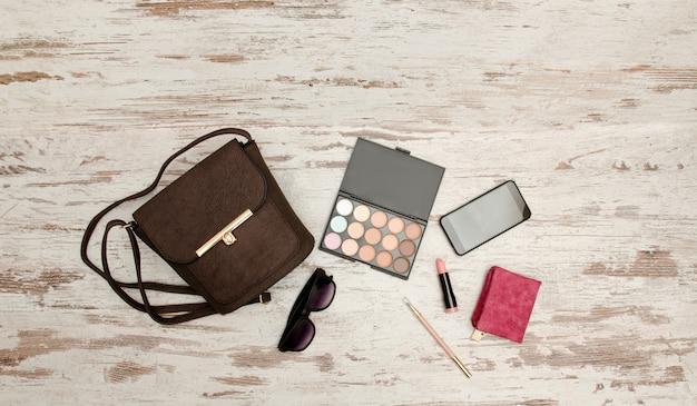 유행 개념. eyeshadows, 핸드백, 안경, 휴대 전화, 립스틱, 나무 배경에 지갑. 평면도