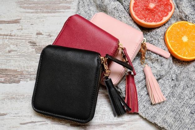 ファッショナブルなコンセプト。セーターと柑橘類の 3 つの女性の財布