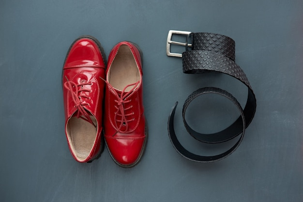 ファッショナブルなコンセプト。トレンディな赤いパテントレザーの靴と灰色の背景にズボンの黒革のベルト。上面図。
