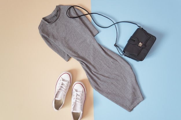 Fashionable concept. women's urban style. gray dress, white sneakers and black handbag on a soft blue background, beige