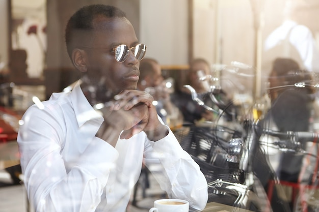 ファッショナブルな自信を持って若い黒ヨーロッパのビジネスマン、思慮深く集中した表情、手を握りしめ、カフェでビジネスパートナーを待っている間に新しいプロジェクトの戦略を考えています。